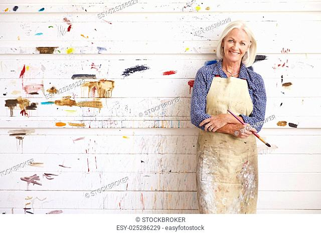 Portrait Of Female Artist Against Paint Covered Wall