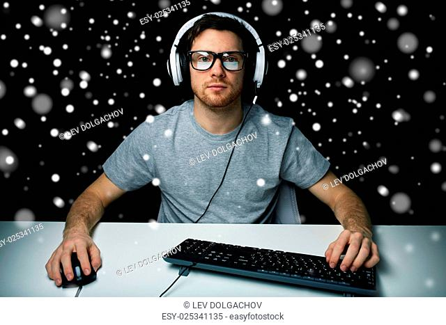 technology, gaming, let's play and people concept - man or hacker in headset and eyeglasses with pc computer playing game and streaming playthrough or...