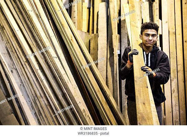 Young man wearing work gloves standing next to a stack of wooden planks in a warehouse, carrying long pieces of wood, looking at camera