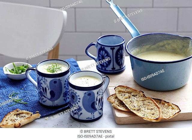 Meal with mugs of leek and potato soup with bread