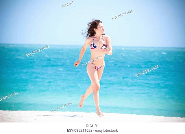 0bdc7cbd9d0 Beautiful fit model wearing a thong bikini and jogging at the gorgeous blue  water beaches of