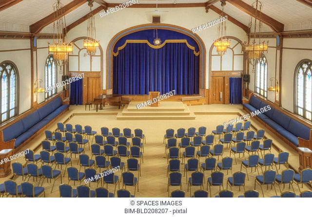 Auditorium with blue chairs, and a stage with curtains