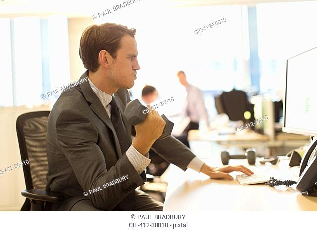 Businessman doing biceps curls with dumbbell at computer in office