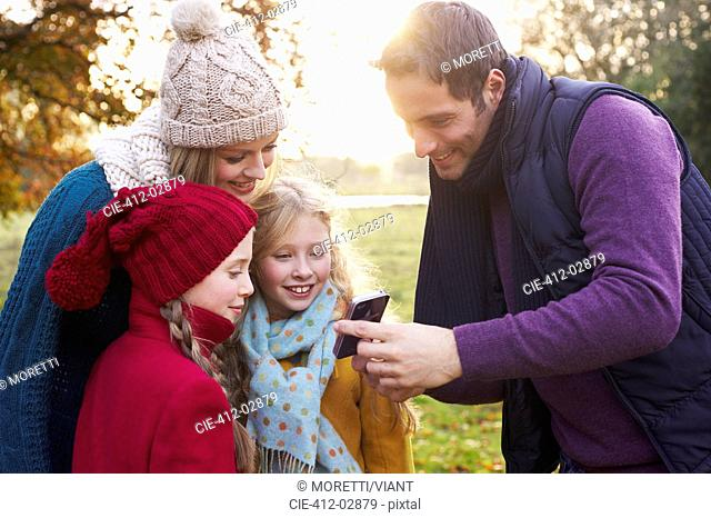 Family using cell phone together outdoors