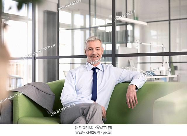 Mature businessman sitting on a couch in the office