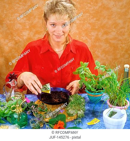 woman sowing cress seeds in bowl