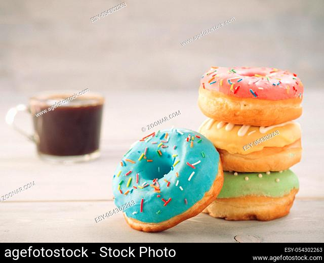 Donuts and coffee on gray wooden table with copy space. Colorful donuts and coffee cup on grey wooden background with copyspace