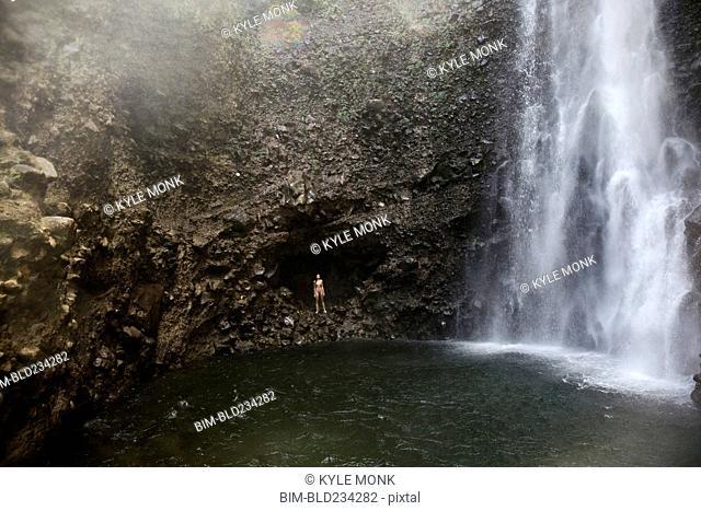 Mixed Race woman standing near waterfall pool