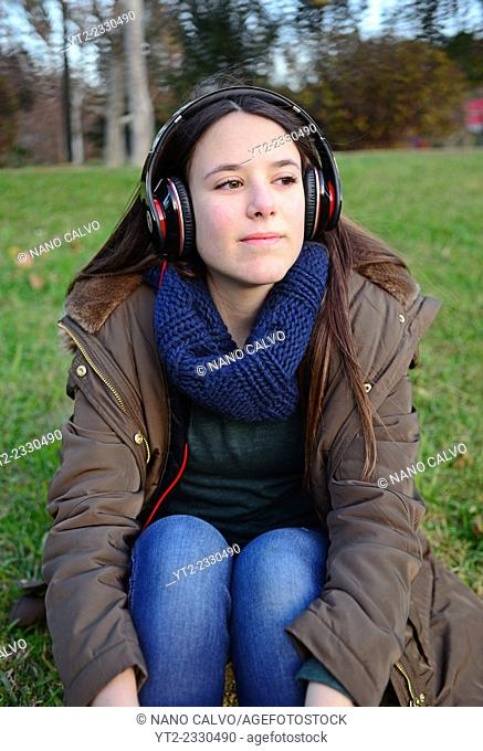 Cute teenager listening to music with headphones in park