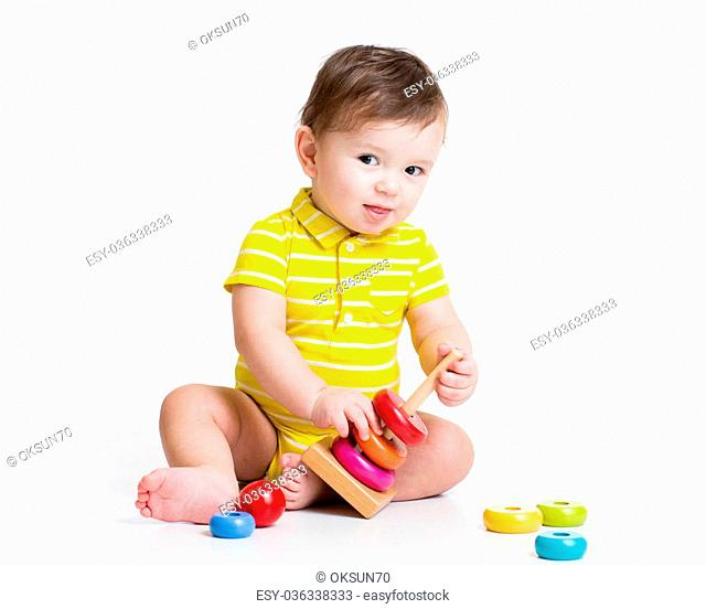 toddler boy playing with colorful toy pyramid