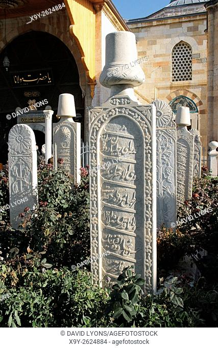 Mevlana Museum, city of Konya, Turkey. Ornate white grave slabs mark the Sufi reed flute and ney players whirling dervish tombs