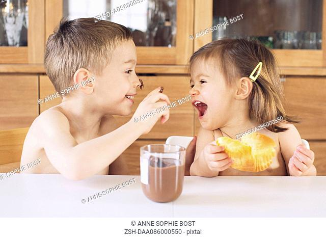 Siblings playing with chocolate spread