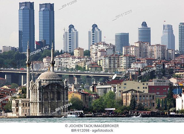 Ortakoey Mosque, officially Bueyuek Mecidiye Camii or Mecidiye Mosque situated on the Bosporus River, district Ortakoey, skyline of modern Istanbul at back