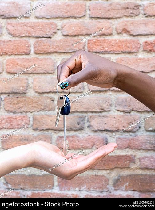 Young woman giving keys to friend by brick wall