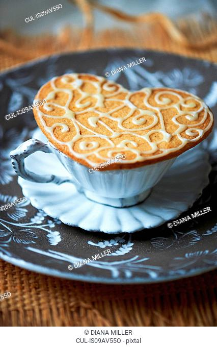 High angle view of heart shaped biscuit on top of vintage tea cup and saucer