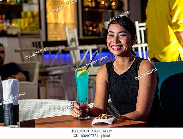 Happy woman having drink in bar