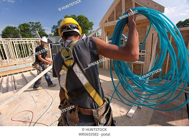 Carpenter unwinding an air hose on the second floor of a house under construction