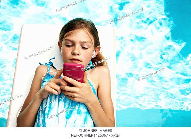 Girl with mp3 player on pool raft