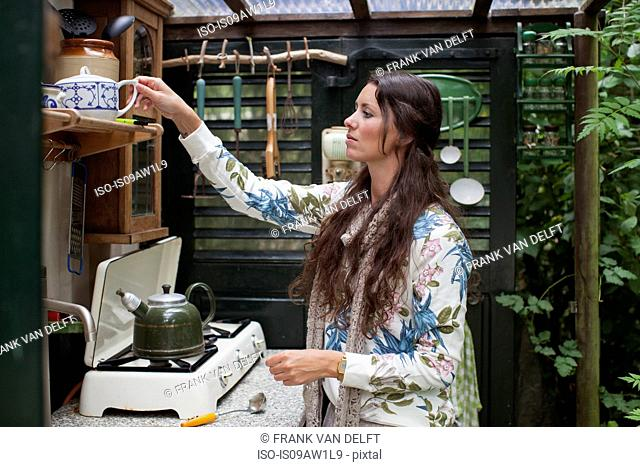 Young woman preparing tea in open cabin kitchen