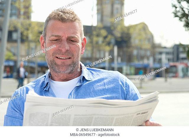 Man, reading newspaper