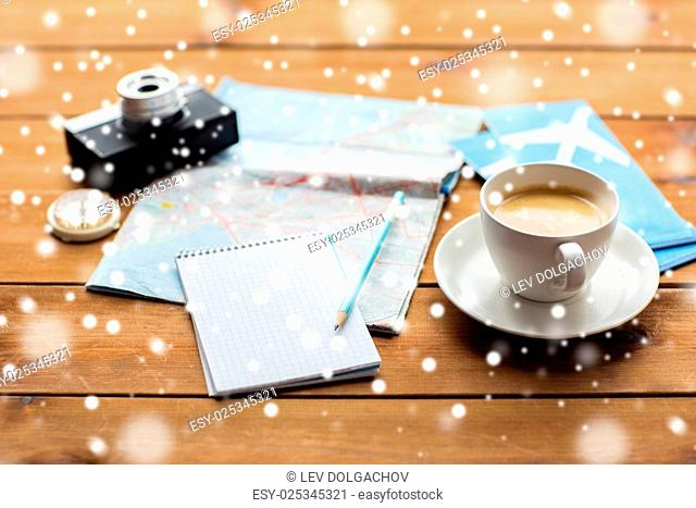 vacation, tourism, travel, winter holidays and objects concept - close up of blank notepad with map, coffee and airplane tickets