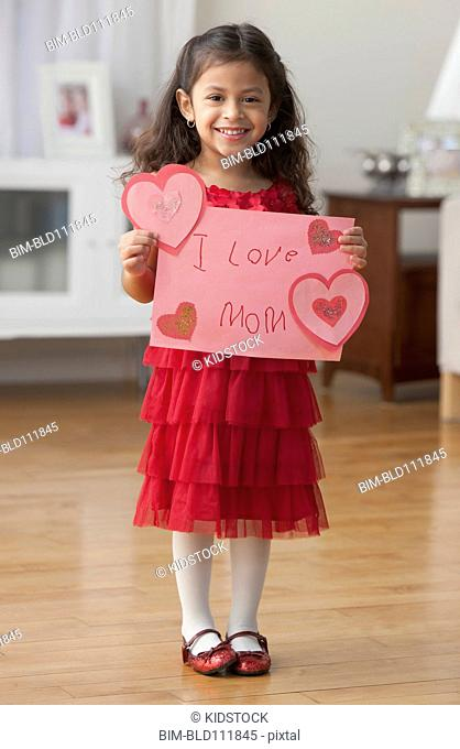 Hispanic girl holding Valentine's card for mother