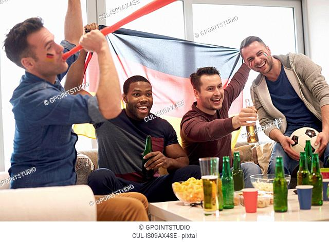 Group of men watching sporting event on television holding German flag and football, celebrating