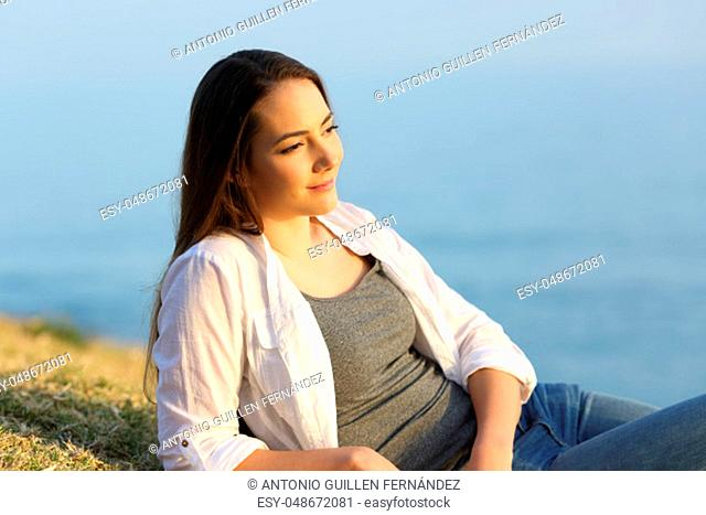 Portrait of a relaxed woman contemplating lying on the grass on a beach