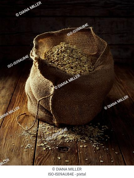 Oats in vintage sack on wooden floor, traditional raw ingredient
