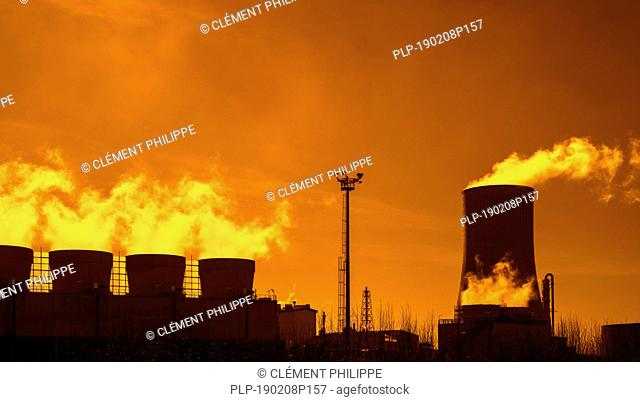 Industrial estate at sunset showing cooling tower and chimneys at the BASF chemical production site in the port of Antwerp, Belgium