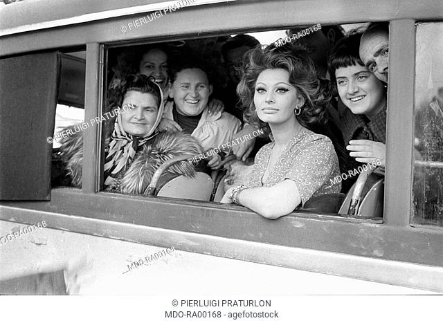 Italian actress Sophia Loren Portrait of a bus full of local people during the filming of Marriage Italian Style. 1964