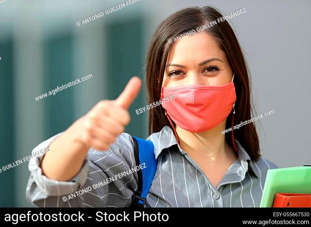 Front view portrait of a happy student wearing mask with thumbs up in the street