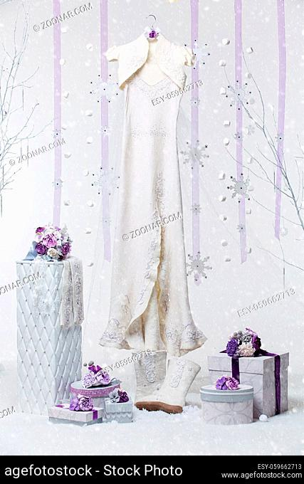 Beautiful felted wool bridal gown with set of stylish wedding accessories in purple tone over snow flakes background. Copy space
