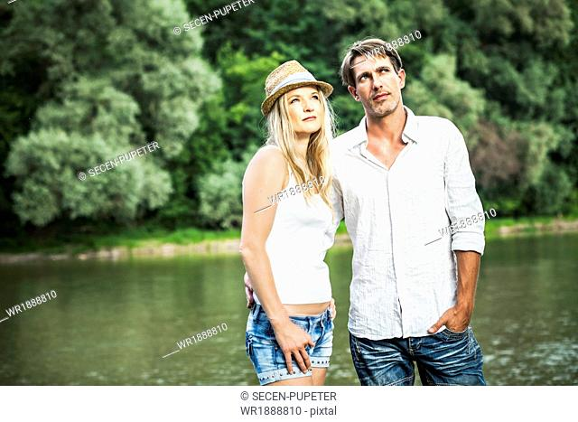 Young couple stands side by side, river in background, Bavaria, Germany
