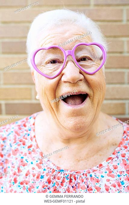 Portrait of happy senior woman wearing heart-shaped glasses pulling funny faces