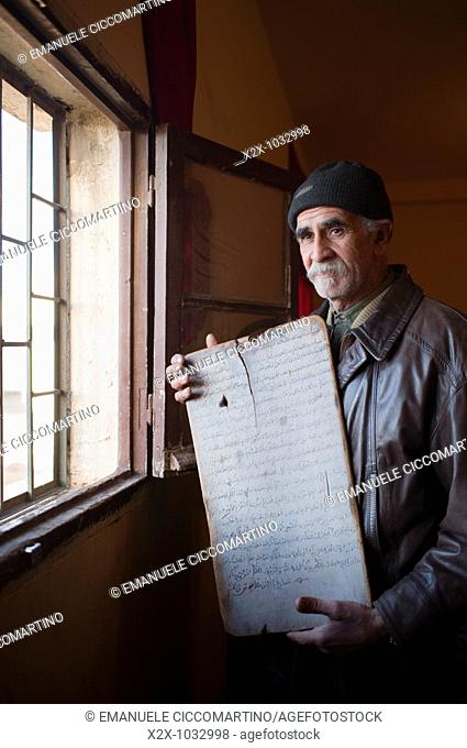 Moroccan man showing a Koranic school ancient board, Oujda, Oriental region, Morocco