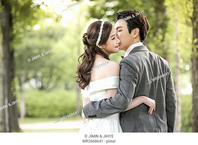 Portrait of young romantic wedding couple posing outdoors