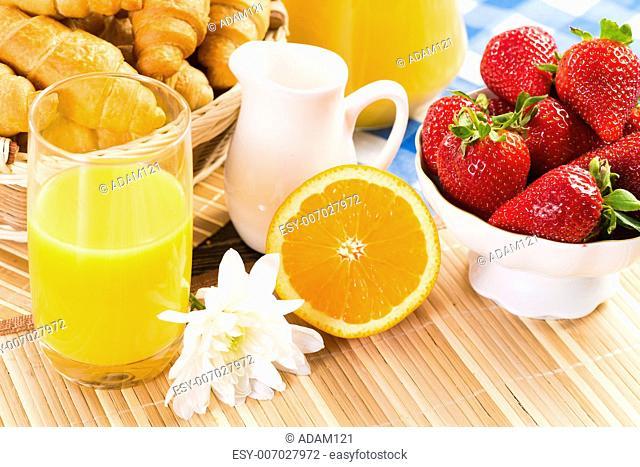 orange juice, croissants and strawberries still life