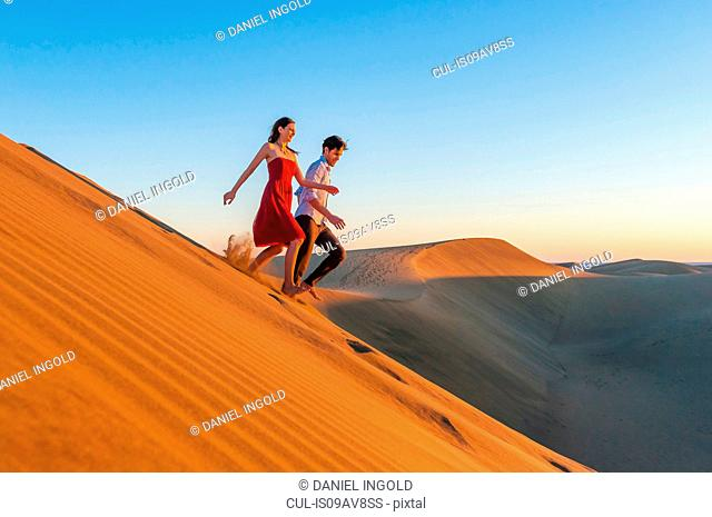 Couple running down sand dune