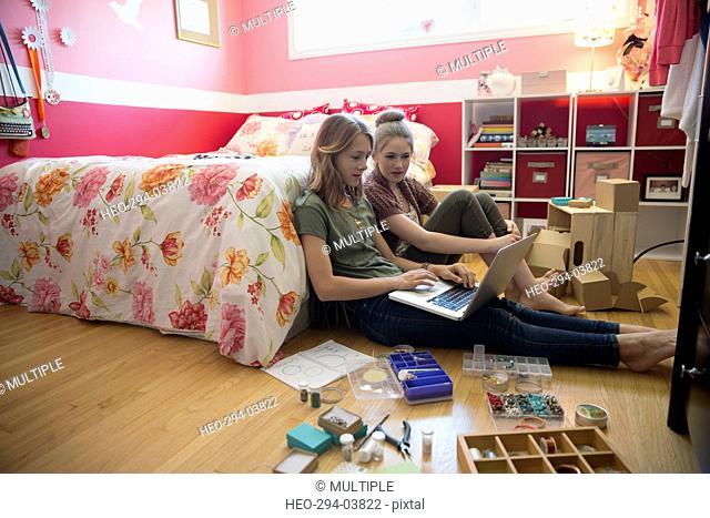 Girls using laptop making jewelry on bedroom floor