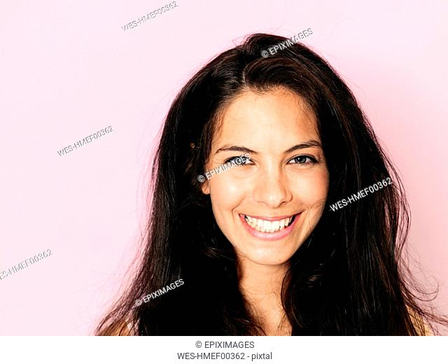 Portrait of young smiling woman with black hair in front of pink background