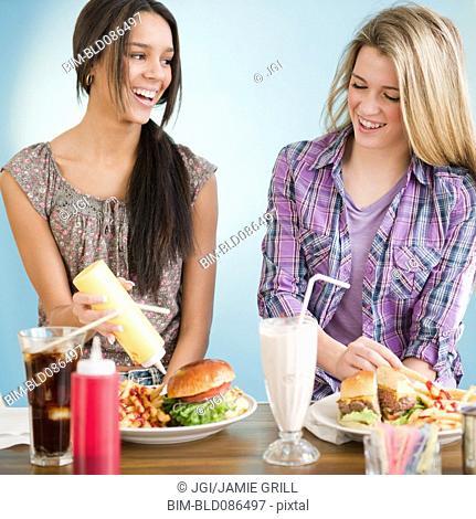 Teenage girls eating hamburgers and french fries