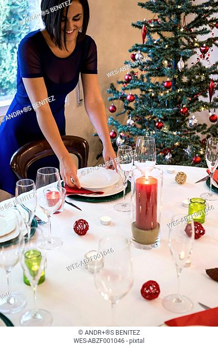 Woman setting the table for Christmas dinner
