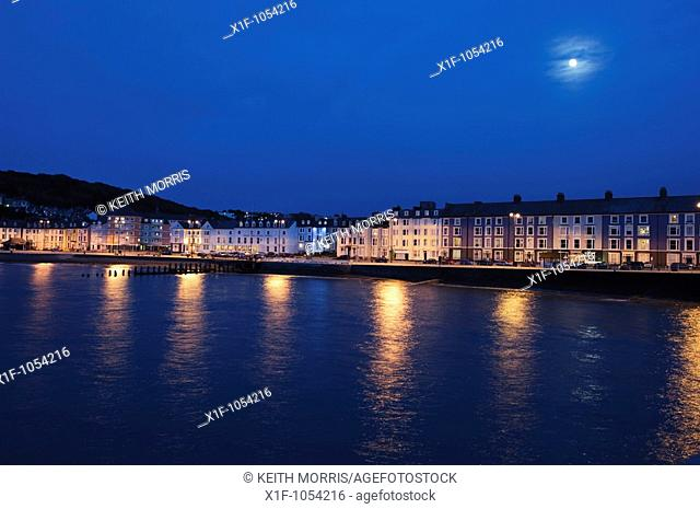 Moon over Aberystwyth promenade and seashore at night, long exposure image, Wales UK
