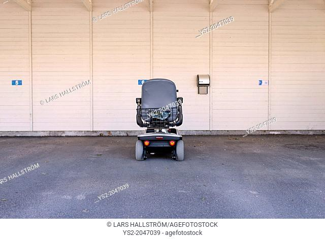 One electric wheelchair alone in a garage. Conceptual image of getting old, disabled and lonely