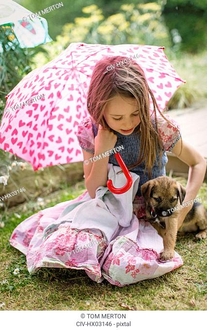 Girl with puppy dog holding heart-shape umbrella in grass