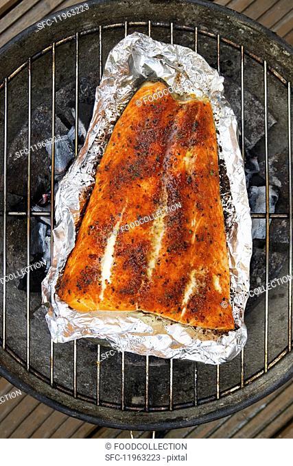 Spiced salmon in aluminium foil on a barbecue
