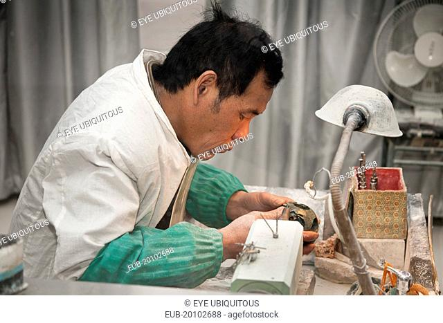 Man manufacturing a jade ornament in a jade factory