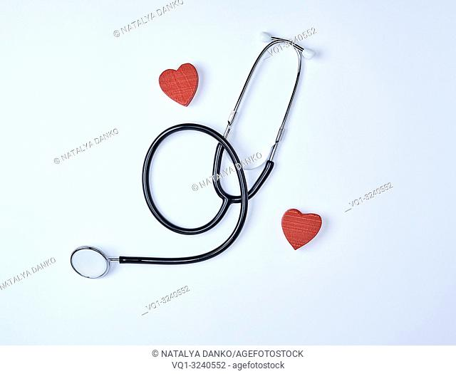 black medical stethoscope and two red wooden hearts on white background