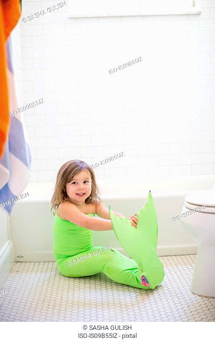 Portrait of girl in lime green mermaid costume sitting on bathroom floor